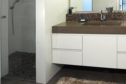 בית דביר-מקלחת הורים. חלוקי אבן שחורים ברצפת מקלחון  פסיפס חום בקירות   תכנון ועיצוב: ליאת דביר-רותם.  צילום: שי אפשטיין.