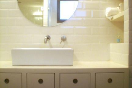 חדר אמבטיה. חדר אמבטיה בתל אביב  קרמיקה 10X20 פאזה לבן  כיור מונח מעל ארון  ברזים: BONGIO-ITALY