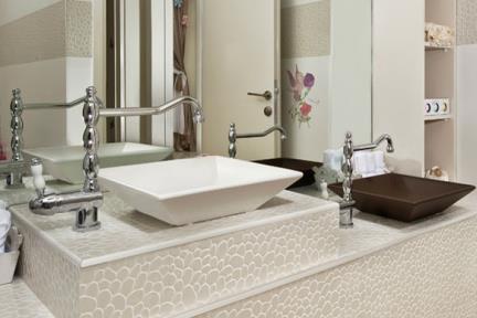 בית בנתניה. עיצוב-אריאלה עזריה  חדר אמבטיה  עם אריחים דמוי חלוקי נחל  כיורים צבעונים