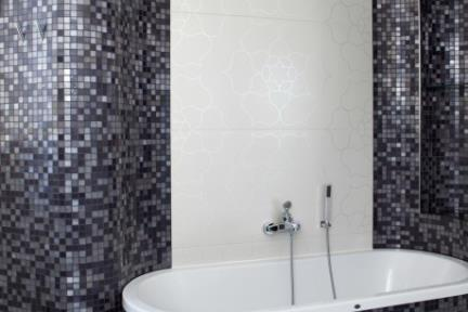 חדר אמבטיה עם חיפוי דמוי פסיפס. לתמונות נוספות