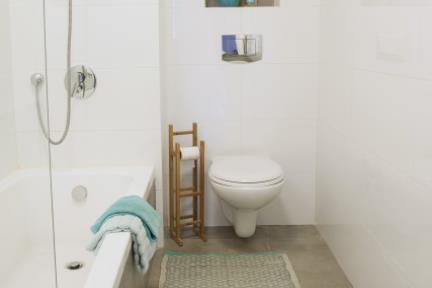בית בסגנון מודרני. מקלחת ילדים, שימוש באריחים דמוי בטון ונגיעות צבע בעזרת אבזור נלווה   צילום: אורית אלפסי.