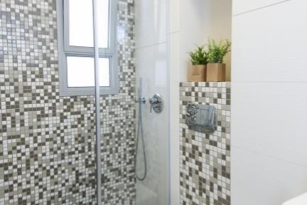 בית בסגנון מודרני. מקלחת הורים, שימוש באריחים דמוי פסיפס ליצירת מקלחת מעניינת.   צילום: אורית אלפסי.