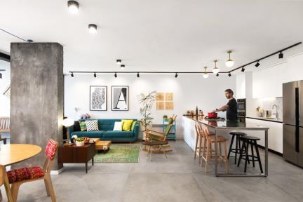 """סלון. בחרנו לדירה ריצוף אבן אפור, גודל האריח 120X120 ס""""מ.  רצינו ליצור תשתית במראה תעשייתי."""